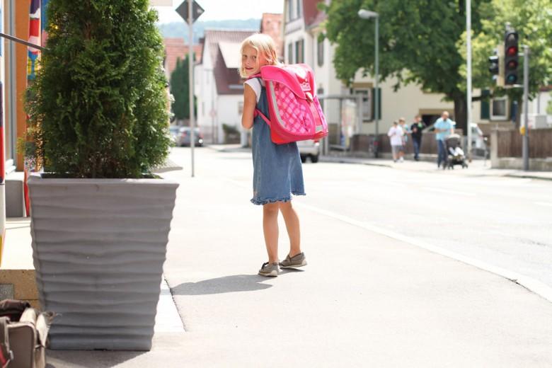 Schulkind läuft mit Rucksack