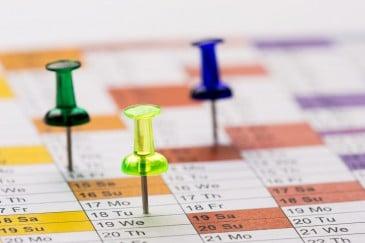 Eventplanung: Kalender mit Stecknadeln auf den Aufgaben und Terminen