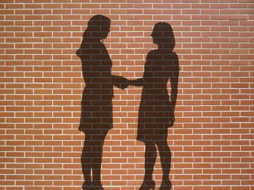 Zwei Menschen schütteln sich im Schatten die Hand